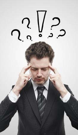 exclamation mark: Retrato de un hombre joven con signo de exclamación y signos de interrogación sobre su cabeza. Imagen conceptual de un hombre de mente abierta. Sobre un fondo gris