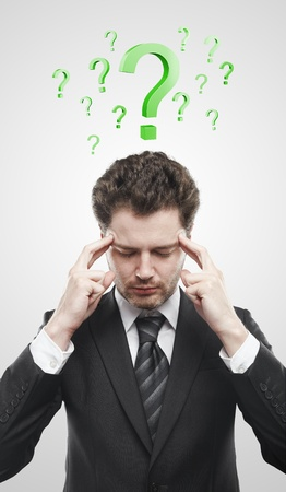 onbeantwoorde: Portret van een jonge man met groene vraagtekens boven zijn head.Conceptual beeld van een open minded man. Stockfoto