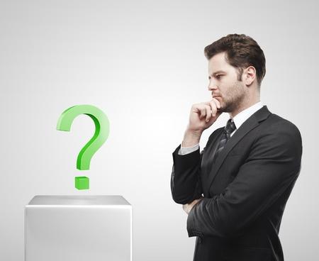 onbeantwoorde: Jonge zakenman blik op de groene vraagtekens op een witte sokkel. Op een grijze achtergrond
