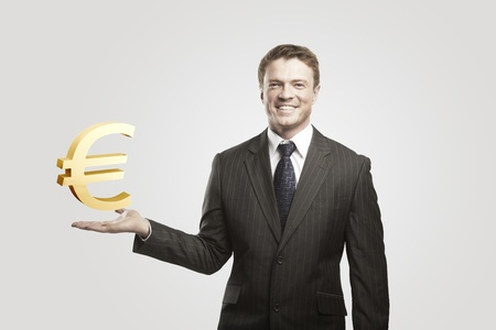 Young  businessman chooses a Gold Euro Sign.On a gray background photo