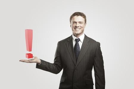 poner atencion: Joven empresario con un signo de exclamación en su hand.On un fondo gris
