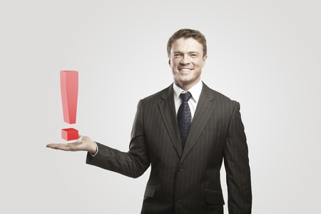 unanswered: Young  businessman with an exclamation mark on his hand.On a gray background