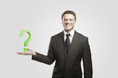 onbeantwoorde: Jonge zakenman met een vraagteken op zijn hand.On een grijze achtergrond