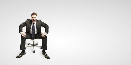 jefe enojado: Hombre de negocios joven gritando y sentado en un chair.On un fondo gris