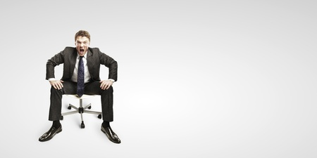 angry boss: Young businessman shouting and sitting on a chair.On a gray background