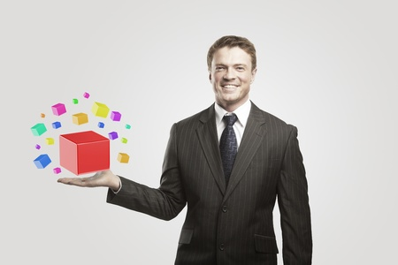unsolvable: Young  businessman with colored boxes. On a gray background
