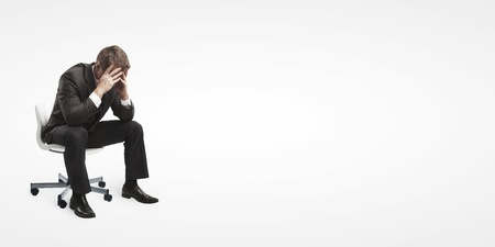 Young businessman sitting on chair with head down as if sad or depressed .Isolated on a white background Stock Photo
