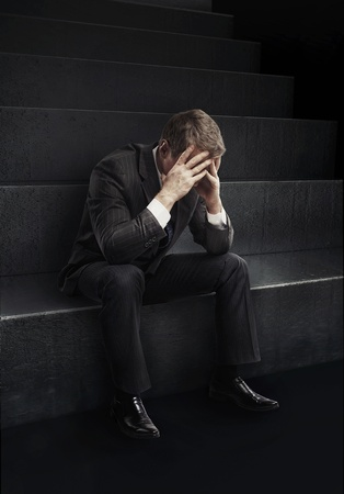 sitting down: Young businessman sitting on stairs with head down as if sad or depressed.