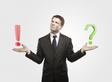 Young  businessman with a question and exclamation mark on his hand.Man makes a choice. On a gray background