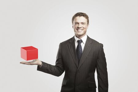 Young  businessman with red box. On a gray background  photo