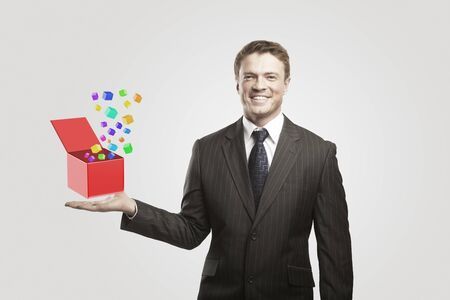 Young  businessman with colored boxes. On a gray background  photo