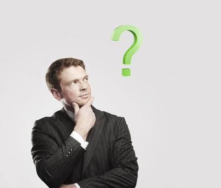 onbeantwoorde: Portret van een jonge man met groene vraagteken boven zijn head.Conceptual beeld van een open-minded man. Op een grijze achtergrond