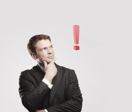 Portrait of a young man with red exclamation mark above his head. Conceptual image of a open minded man.  On a gray background photo