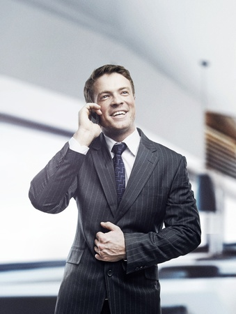 only young men: Portrait of happy businessman talking on mobile standing in office, smiling.