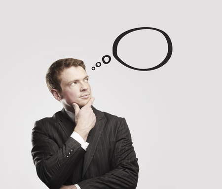 Young businessman with speech bubbles inside. Thinking man. Conceptual image of a open minded man.On a gray background photo