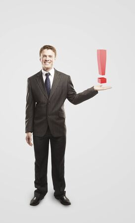 unanswered:  Young  businessman with an exclamation mark on his hand.On a gray background  Stock Photo