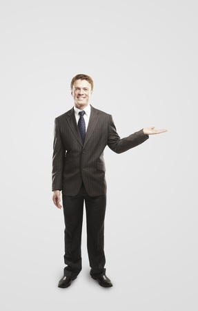 Smiling young  businessman presenting something on empty hand. On a gray background photo