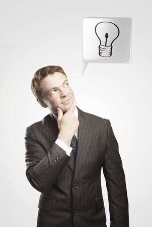 Portrait of a young man with light bulb above his head. Man coming up with an idea. On a gray background Stock Photo - 11286453