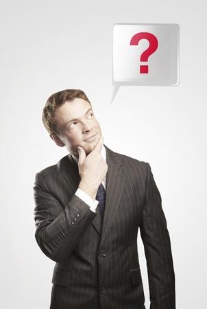 onbeantwoorde: Portret van een jonge man met een vraagteken boven zijn head.Conceptual beeld van een open minded man. Op een grijze achtergrond Stockfoto
