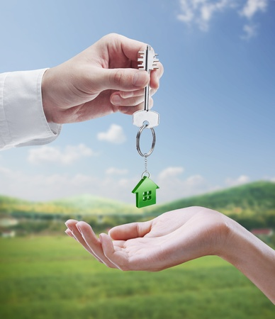 Man is handing a house key to a woman.Key with a keychain in the shape of the house. On background of nature Stock Photo - 11286415