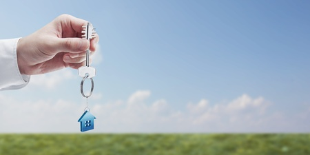 Hand holding key with a keychain in the shape of the house. House key on background of nature photo