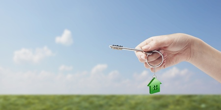 Hand holding key with a keychain in the shape of the house. House key on background of nature Stock Photo - 11286422