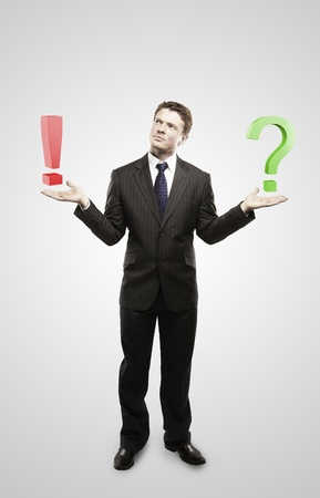 punctuation: Young  businessman with a question and exclamation mark on his hand.Man makes a choice. On a gray background