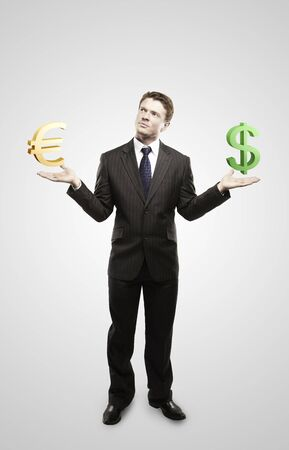 Young  businessman chooses euro or dollar signs. On a gray background photo
