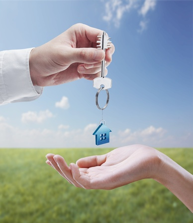 Man is handing a house key to a woman.Key with a keychain in the shape of the house. On background of nature photo