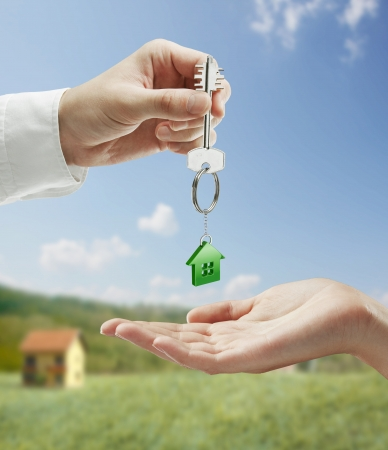 agents: Man is handing a house key to a woman.Key with a keychain in the shape of the house. On background of nature Stock Photo