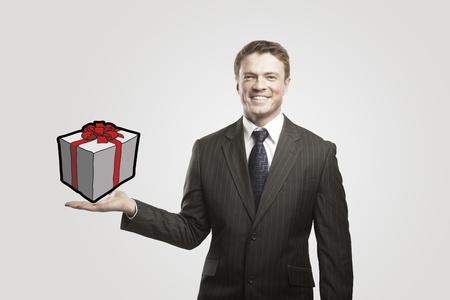 Young  businessman with a gift on his hand. On a gray background. photo