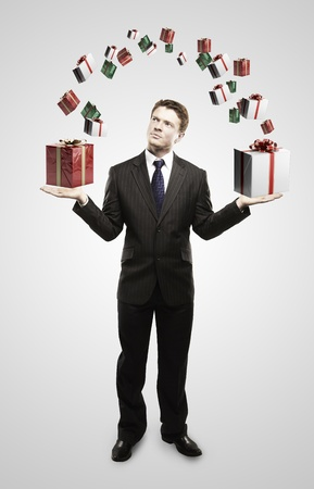 Young  businessman with a gift boxes in his hands. On a gray background. photo