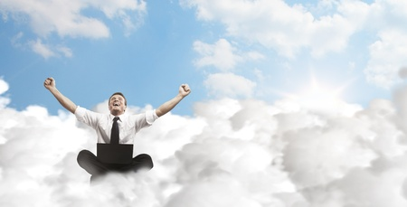 technology deal: Happy young businessman with laptop sitting on the clouds. Stock Photo