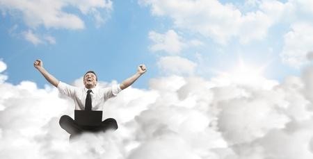 Heureux jeune homme d'affaires avec un ordinateur portable assis sur les nuages. Banque d'images