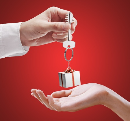 keychain: Man is handing a house key to a woman. Key with a keychain in the shape of the gift box. House key on a red background. Stock Photo