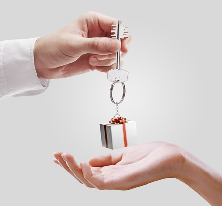 Man is handing a house key to a woman. Key with a keychain in the shape of the gift box. House key on a gray background. photo