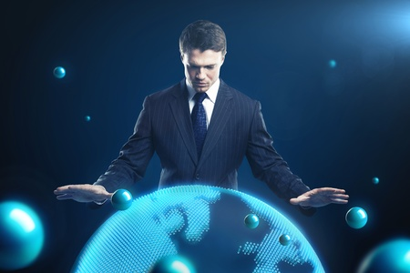 Man is controlling the earth models. Young business man with planet system around him.  Conceptual image of technology global communication photo