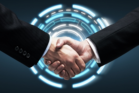 technology deal: Handshake - Hands holding on background  a touch screen interface Stock Photo