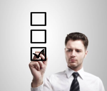 Young business man drawing a tick on a glass window in an office. Man choosing one of three options.On a gray background photo