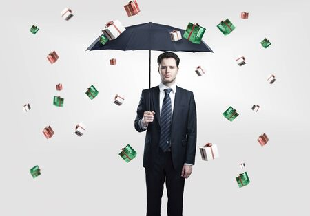 Young Business man with umbrella under gift boxes rain. On a gray background. photo