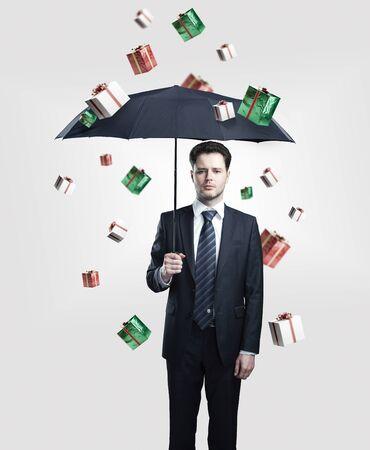 dar un regalo: Hombre de negocios joven con paraguas bajo la lluvia cajas de regalo. Sobre un fondo gris.