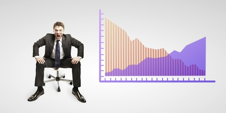 decline: Young business man shouting and sitting on a chair with a graphs showing rise and fall in profits or earnings, falling orange.  Financial diagrams. Rising arrow, representing business growth.  Stock Photo