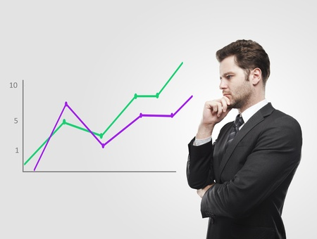Young business man look at a graph. Rising arrow, representing business growth. On a gray background photo
