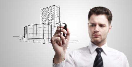 arquitecto: Joven hombre de negocios la elaboraci�n de un proyecto de construcci�n de una ventana de cristal. Retrato de joven arquitecto pensamiento acerca de la construcci�n. Sobre un fondo gris.
