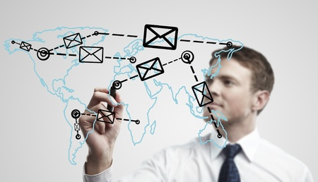 Young business man drawing a global network with envelopes on world map. Man drawing  E-mail Icon on a glass window.  The metaphor of international communication around the world. On a gray background. Stock Photo - 11499099