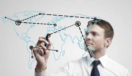 a window on the world: Young business man drawing a global network or globalization concept on world map.  Man drawing internet diagram or business connection on a glass window. On a gray background. Stock Photo