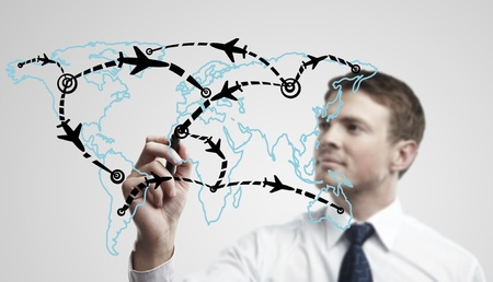 Young business man drawing an airplane routes on world map. Man drawing world map with aircraft flying on a glass window. The metaphor of international air travel around the world, travel to anywhere on the planet Earth and the workload of air traffic photo