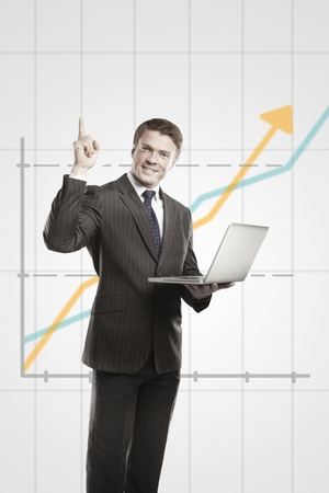 Happy young business man with laptop showing thumbs up.  On a gray background with rising arrow, representing business growth Stock Photo - 11499103