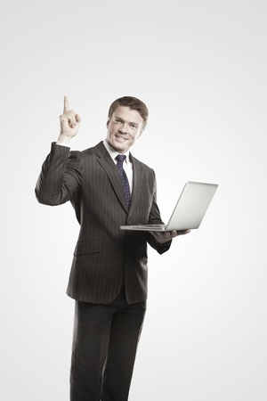 Happy young business man with laptop showing thumbs up. On a gray background. Stock Photo - 11499101