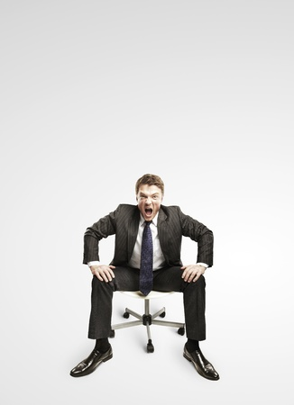 Young businessman shouting and sitting on a chair. On a gray background photo
